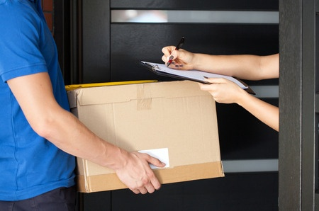 Delivery guy holding package while woman is signing documents